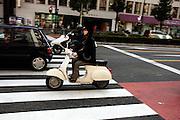 Met een iPod in haar oren rijdt een meisje op een brommer door Tokyo