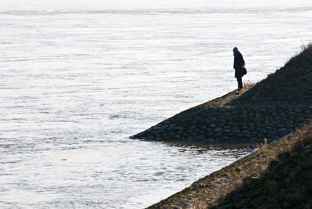 DEU,Köln,NRW,Nordrhein-Westfalen, Eine Frau steht  bei kühlem Wetter an einem mit Steinen befestigten Ufer des Rheins    |  woman standing at the banks of the river Rhine in Cologne    |