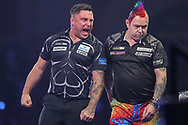 Gerwyn Price celebrates winning the second set and bumps into Peter Wright during the PDC William Hill World Darts Championship Semi-Final at Alexandra Palace, London, United Kingdom on 30 December 2019.