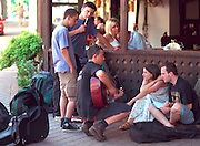 Travelers age 20 through 24 relaxing and enjoying guitar music.  Zakopane Poland