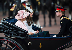 © London News Pictures.. 14/06/2014. Camilla, Duchess of Cornwall (left), Catherine, Duchess of Cambridge (centre) and Prince Harry (right) , riding in a carriage from Buckingham Palace during the annual Trooping the Colour Ceremony in central London. The event marks the queens official birthday. . Photo credit:Ben Cawthra/LNP