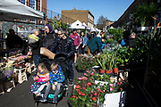 Children being pushed through Columbia Road flower market on Mothers Day, and its last open Sunday for a while due to Covid-19 on what would normally be a busy, bustling market day with hoards of people out to buy flowers and socialise, the numbers of people out is a fraction of a regular Sunday on 22nd March 2020 in London, England, United Kingdom. All of the East End Sunday markets have been affected by the Coronavirus outbreak, with some completely closed and some currently partially open. Coronavirus or Covid-19 is a new respiratory illness that has not previously been seen in humans. While much or Europe has been placed into lockdown, the UK government has announced more stringent rules as part of their long term strategy, and in particular social distancing.