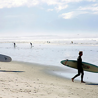 Africa, South Africa, Muizenberg.  Surfers at Muizenberg Beach on the Cape peninsula, near Cape Town.
