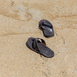 Berlin, MD - July 11, 2016:  A pair of sandals on the beach at the Assateague Island National Seashore.