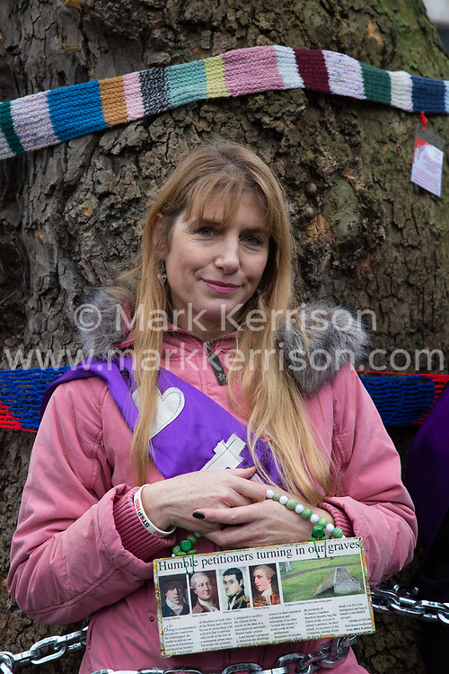London, UK. 12th January, 2018. Local resident Jo Hurford stands chained to a tree outside Euston station during a protest against the HS2 high-speed rail link. The protest formed part of a campaign by local residents against the planned felling of mature London Plane, Red Oak, Common Whitebeam, Common Lime and Wild Service trees in Euston Square Gardens to make way for temporary HS2 sites for construction vehicles and a displaced taxi rank.