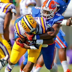 Oct 12, 2013; Baton Rouge, LA, USA; Florida Gators defensive end Dante Fowler Jr. (6) tackles LSU Tigers running back Kenny Hilliard (27) during the first quarter of a game at Tiger Stadium. Mandatory Credit: Derick E. Hingle-USA TODAY Sports