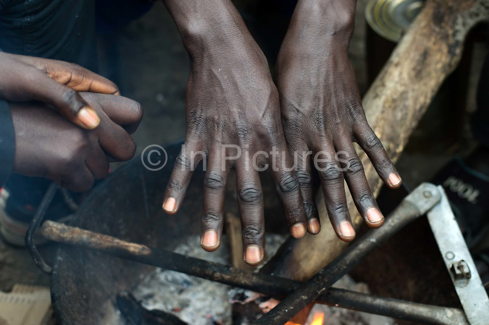 France. Refugees. Calais. So-called Jungle camp . Sudanese refugees warm their hands over a small stick fire, trying to keep warm..