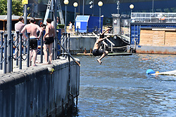 © Licensed to London News Pictures. 25/06/2020.  London UK: Londoners take to the beach at the Royal Victoria Dock in Newham, East London on the hottest day of the year so far. Teenagers jump in to the chilling waters at the man made beach, Photo credit: Steve Poston/LNP
