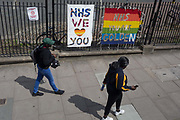 As the UKs Coronavirus death toll during the governments social distancing lockdown, rose by 384 to 33,998, and the R rate of infection is reported to be between 0.7 and 1.0, south Londoners walk past thank you banners for key workers in the NHS National Health Service outside the Maudsley Hospital in Camberwell, on 15th May 2020, in London, England.