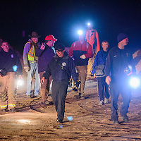 Marina Orlovskaya, center, is escorted out of the Pyramid Rock trailhead by police, firefighters and search & rescue volunteers at Red Rock Park in Gallup Tuesday. Orlovskaya said she was traveling from Florida to Arizona and decided to hike the trail while stopped in Gallup. The 53-year-old Russia native got turned around on the trail and called emergency services when the sun went down and the temperature began to drop. Rescue personnel located Orlovskaya and her two dogs about two hours after the initial phone call and safely returned her to the trailhead.