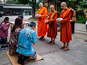 13 JANUARY 2019 - NAKHON PATHOM, THAILAND:  A family prays while the female monks from Wat Songdhammakalyani chant after the family gave the monks alms during the alms rounds. The Sangha Supreme Council, Thailand's governing body of Buddhist monks, bans the ordination of female monks, but hundreds of Thai women have gone abroad, mostly to Sri Lanka and India, to be ordained. There are about 270 women monks in Thailand and about 250,000 male monks. There are 7 monks and 6 novices at Wat Songdhammakalyani in Nakhon Pathom. It was the first temple in Thailand to have female monks. The temple opened 60 years ago and has always been a temple of women monks. Women can be ordained as novices in Thailand, but to be ordained as a full monk would require the participation of 10 female monks and 10 male monks, and male monks in Thailand are barred from participating in women's ordination ceremonies.     PHOTO BY JACK KURTZ