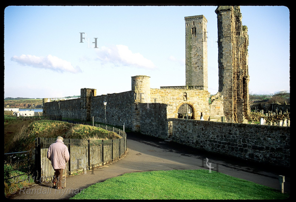 Man with cane walks path toward church ruins and cemetery on an April afternoon in St. Andrews. Scotland