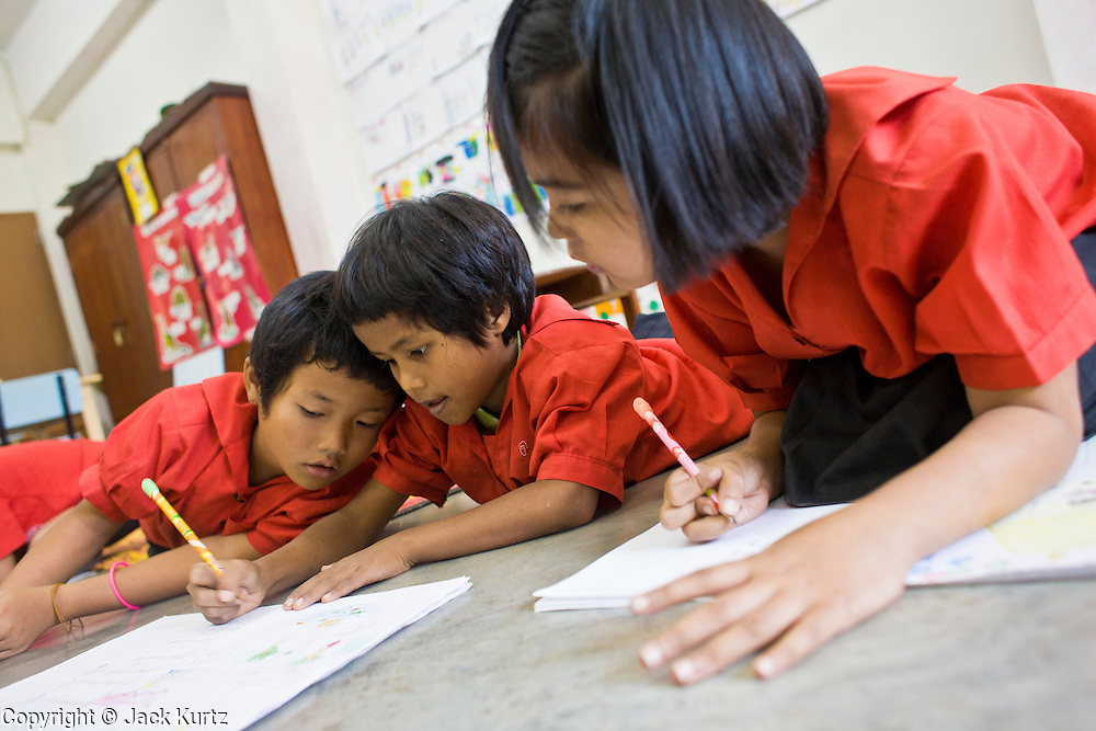"""19 FEBRUARY 2008 -- SANGKLABURI, KANCHANABURI, THAILAND: Burmese refugee children study Thai in a first grade class at Baan Unrak School. Classes at the school are taught in Thai, but many of the refugee children don't speak Thai so they have to take remedial classes. Baan Unrak children's home and school, established in 1991 in Sangklaburi, Thailand, gives destitute children and mothers a home and career training for a better future. Baan Unrak, the """"Home of Joy,"""" provides basic needs to well over 100 children, and  abandoned mothers. The home is funded by donations and the proceeds from the weaving and sewing shops at the home. The home is a few kilometers from the Burmese border. All of the women and children at the home are refugees from political violence and extreme poverty in Burma, most are Karen hill tribe people, the others are Mon hill tribe people. The home was started in 1991 when Didi Devamala went to Sangklaburi to start an agricultural project. An abandoned wife asked Devmala to help her take care of her child. Devmala took the child in and soon other Burmese women approached her looking for help.    Photo by Jack Kurtz"""