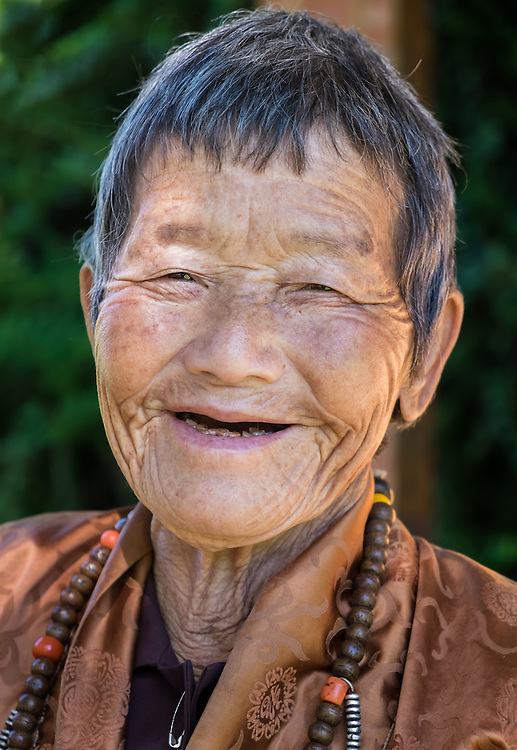 THIMPHU, BHUTAN - CIRCA OCTOBER 2014: Old Bhutanese woman smiling close to the Memorial Chorten in Thimphu