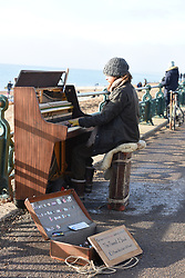 © Licensed to London News Pictures. 10/01/2021. Brighton, UK. A busker with a piano entertains visitors to the seafront at Brighton on the south coast during the third national lockdown. Photo credit: Liz Pearce/LNP