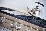 Stainless Steel Gas Range Cooktop and Chrome Teapot Stock Photo
