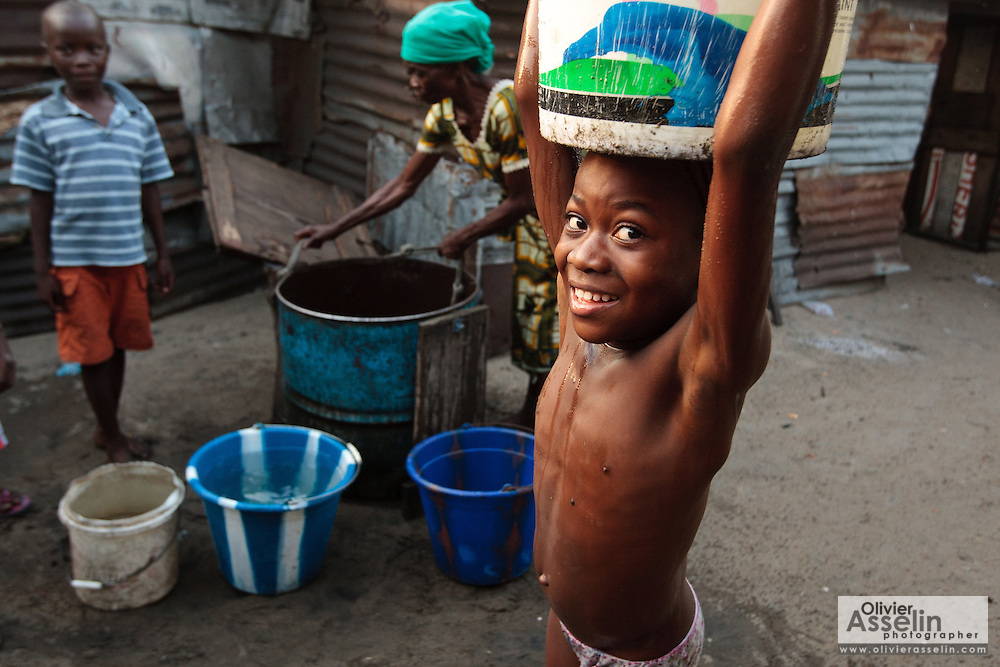 A girl carries a bucket of water she just filled from a well in the West Point slum in Monrovia, Montserrado county, Liberia on Monday April 2, 2012.