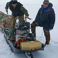North of the Arctic Circle in Russia, a nomadic Komi reindeer herder struggles to start an aging Russian snowmobile used by journalists covering their migration. Most men in the group have high mechanical skills after serving their mandatory two years in the military.  Ironically, the annual top prize for a regional reindeer-sled race is a snowmobile!