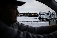 Mike Connelly, a Certified Nursing Assistant (CNA) working in North Dakota in support of the Dakota Access Pipeline, drives past oil tankers being transported by railroad within the Bakken Formation in Glendive, Montana near the North Dakota border in January 2017.<br /> <br /> Connelly's support for the Dakota Access Pipeline is based on North Dakota's oil-heavy economy and the pipeline's creation of employment to individuals in the oil business sector who are struggling to find opportunities to sustain their families following the 2015 Bakken oil bust. Connelly's experience as a travel CNA adds to his strong belief in the reduction of road accidents and deaths on North Dakota's dangerous roads if the pipeline is constructed, reducing the number of vehicles transporting oil through the state.