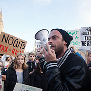 Jolyon Rubenstein speaks on the grass in Parliament Square. The marching students breached the fence surrounding Parliament Square and the police lines. A small group stayed on the square while the main part moved on the planned rally nearby. Thousands of students turned out to a march against fees and cuts in the education sector, calling for workers ans students to unite againts the Government's austerity policies.