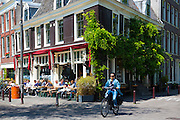 Young oman cycling past Cafe Thiessen on Brouwersgracht, Amsterdam, The Netherlands