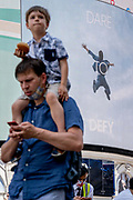 An image of a leaping figure from a Piccadilly Circus Calvin Klein ad whose slogan is 'Dare to Defy', and a man with a child on his shoulders on Covid 'Freedom Day'. This date is what Prime Minister Boris Johnson's UK government has set as the end of strict Covid pandemic social distancing conditions with the end of mandatory face coverings in shops and public transport, on 19th July 2021, in London, England.