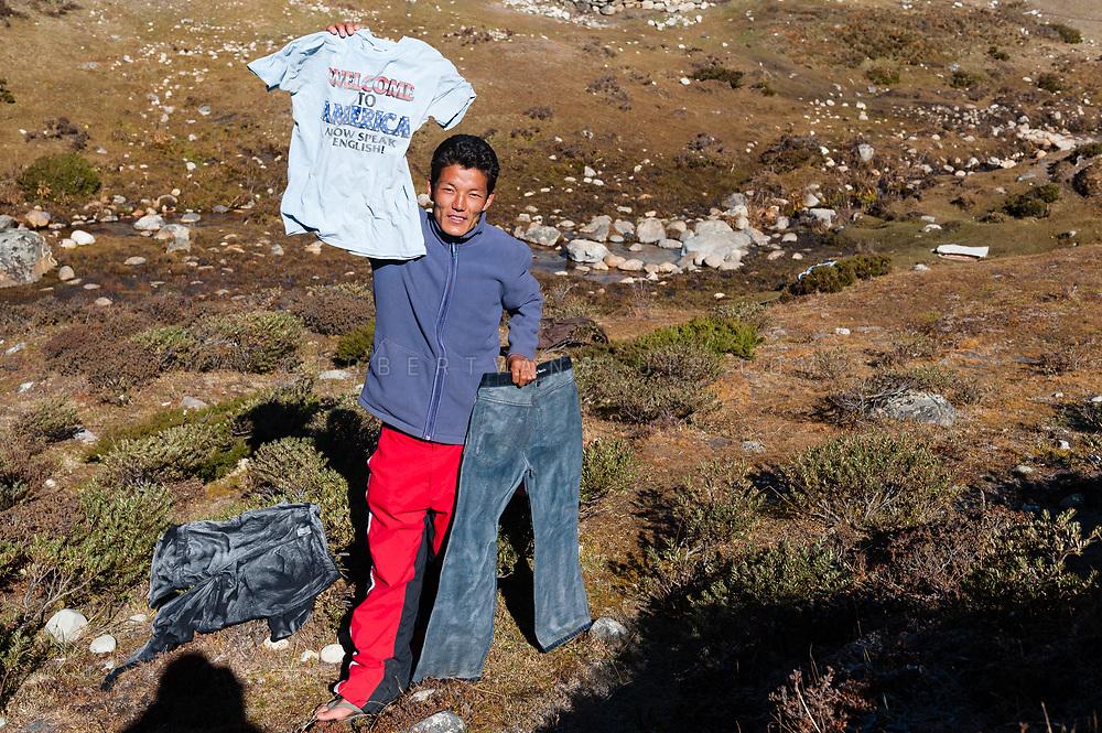 Trekking guide showing frozen laundry in Pheriche, Nepal. Photo © robertvansluis.com