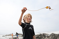 A blonde boy plays with seaweed on the beach at Lincoln, City Oregon