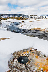 A small bubbling hot and the Firehole River winding through the Yellowstone's Upper Geyser Basin near Old Faithful.  In Winter you can only get here by snowcoach or Snowmobile, it is a wonderful time.