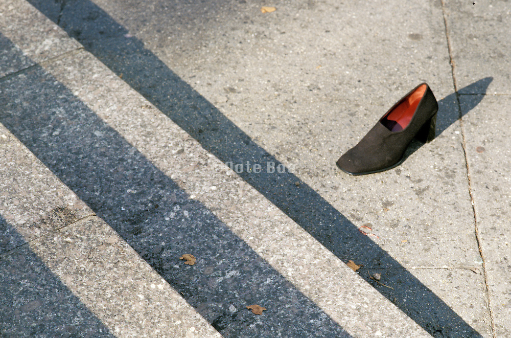 one lonely woman?s shoe on city street