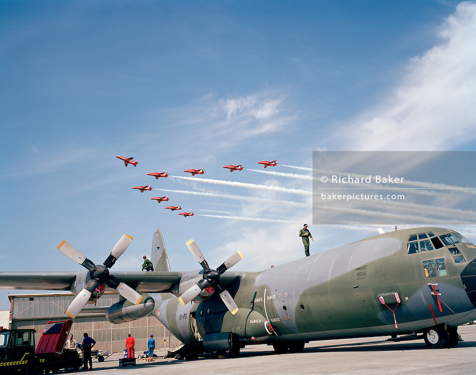 A pilot of the French Air Force walks looking down along the fuselage of his C-130 Hercules oblivious to nine Hawk jet aircraft of the elite 'Red Arrows', Britain's prestigious Royal Air Force aerobatic team, who come screaming behind and 'breaking to land'. This set procedure prepares them to split up as a group, peel off seperately and land safely at the Payerne Air 04 show, Switzerland. It is a perfect day for aerobatics with blue alpine skies during the teams' two-day visit to the Swiss airfield. Payerne is home of the Swiss Air Force who host the cream of international aerobatic display flying every September to 275,000 spectators over a weekend. European display teams and air forces gathered to celebrate the 90th anniversary of Swiss military aviation. .