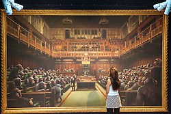 "© Licensed to London News Pictures. 27/09/2019. London, UK. A staff member view 'Banksy's artwork titled ""Dystopian View of The House of Commons Comes to London"" Est -£1.5 – £2 million during the preview of Sotheby's Frieze Week Contemporary Art Sale. The auction will take place on 3rd October 2019.  Photo credit: Dinendra Haria/LNP"