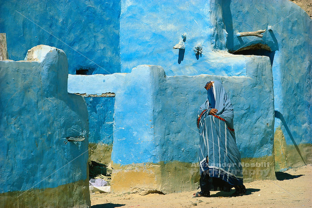 Egypt, 1999 - A woman, wrapped in the traditional blue robes of the Siwa Oasis, enters her family home. In her blue robe she blends in perfectly with the surrounding buildings.