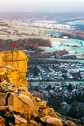 © Licensed to London News Pictures. 25/01/2021. Ilkley UK. A man stands on top of the cow & calf rocks 1,319 ft above sea level looking over the town of Ilkley in Yorkshire as the sun rises this morning. Photo credit: Andrew McCaren/LNP