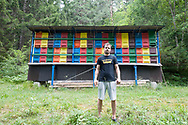 Beekeeper Erik Luznar with some of his hives in the Draga Valley, near Radovljica, Slovenia © Rudolf Abraham