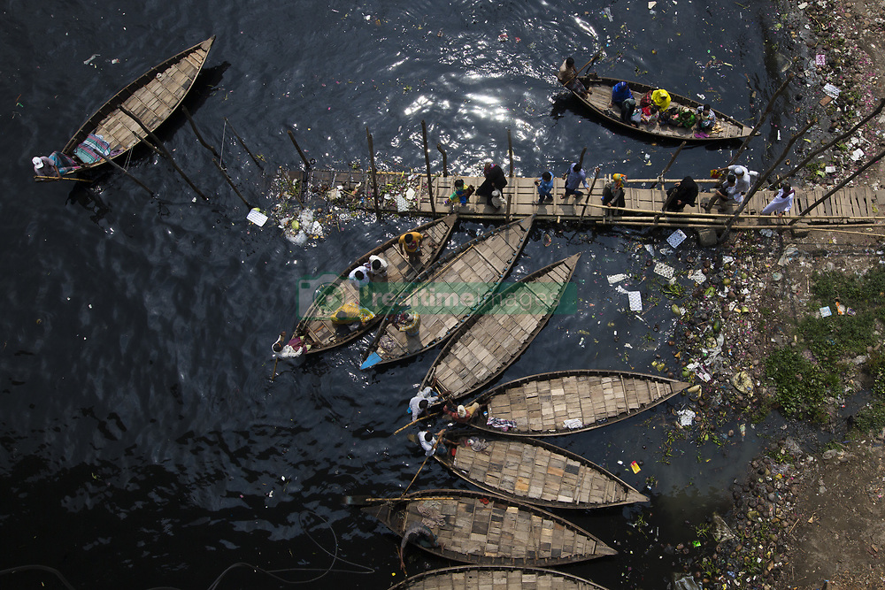 April 17, 2018 - Dhaka, Bangladesh - DHAKA, BANGLADESH - APRIL 17 : Bangladeshi commuters use boats to cross the Buriganga River in Dhaka, Bangladesh on April 17, 2018...The chemical waste of mills and factories, household waste eventually makes its way into the Buriganga River, which is considered to be Dhaka's lifeline. Thousands of people depend on the river daily for bathing, washing clothes, irrigation of food and transportation of goods. The river has suffered extreme biodiversity loss and has now turned black. A large swathe of the Buriganga River, which is the lifeline of the capital, has turned pitch-black with toxic waste, oil and chemicals flowing into it from industrial units. The water became extremely polluted and represents a health hazard for the riverbed communities (Credit Image: © Zakir Hossain Chowdhury via ZUMA Wire)