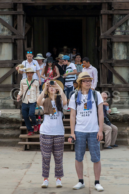 Two Asian toursits with Potato Head t-shirts outside one of the doorways in the ancient Angkor Wat temple grounds Siem Reap, Cambodia.  Angkor Wat is one of UNESCO's world heritage sites. It is Cambodia's main tourist attraction and there are lots of tourists in the background.
