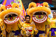 """05 JULY 2014 - BANGKOK, THAILAND: Chinese style lion dancers wait to perform on a side street in Bangkok during a parade for vassa. Vassa, called """"phansa"""" in Thai, marks the beginning of the three months long Buddhist rains retreat when monks and novices stay in the temple for periods of intense meditation. Vassa officially starts July 11 but temples across Bangkok are holding events to mark the holiday all week.    PHOTO BY JACK KURTZ"""
