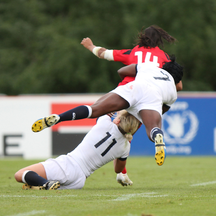 Claire Allan and Maggie Alphonsi tackle Magali Harvey. England v Canada Pool A match at WRWC 2014 at Centre National de Rugby, Marcoussis, France, on 9th August 2014