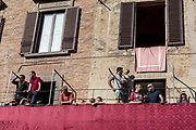 """Italy, Siena, the Palio: If you want to see the Palio you can choose among the wooden Seats called """"Palchi"""" (all around the square), the windows of the Palaces on the Square and the balconies. The last are very few and, as they have a higher position and better view, like the windows,  they are more expensive. The balconies can accommodate up 2 rows of people (the first have chairs the second just stand). The windows are managed directly by the owners of the Palaces in the Campo Square or by the same Palio Business Men."""