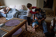 Momen Alsaloum, 22, feeds son Riad, 1, as Riad's brother Amin, 3, vies for attention in one of the family's permanent apartments in Tampa, Florida, U.S. Riad Alsaloum, weak from cancer, rests behind them.