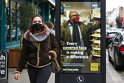 © Licensed to London News Pictures. 26/03/2021. London, UK. A woman wearing a protective face covering walks past the government's 'Every covered face is making a difference' poster in north London as MPs voted to extended emergency Covid-19 powers for another 6 months. The next key date for restrictions easing is Monday 29 March 2021, when the 'Stay at Home' guidance will be dropped. Photo credit: Dinendra Haria/LNP