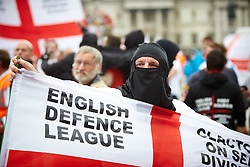 © Licensed to London News Pictures.  20/09/2014. LONDON, UK. A  member of the English Defence League (EDL) pictured wearing a burka during a march down Whitehall to Downing Street. The group is attempting to highlight it belief that  Muslim sexual grooming gangs are abusing English girls. Earlier this week a home office official warned of the rise of the far right. Photo credit: Cliff Hide/LNP