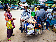 05 JULY 2017 - POIPET, CAMBODIA:  A woman in Poipet begs for money from Cambodian migrant workers who just returned to Cambodia from neighboring Thailand. The Thai government proposed new rules for foreign workers recently. The new rules include fines of between 400,000 and 800,00 Thai Baht ($12,000 - $24,000 US) and jail sentences of up to five years for illegal workers and people who hire illegal workers. Hundreds of companies fired their Cambodian and Burmese workers and tens of thousands of workers left Thailand to return to their countries of origin. Employers and human rights activists complained about the severity of the punishment and sudden implementation of the rules. On Tuesday, 4 July, the Thai government suspended the new rules for 180 days and the Cambodian and Myanmar governments urged their citizens to stay in Thailand, but the exodus of workers continued through Wednesday.    PHOTO BY JACK KURTZ