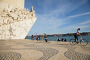 People enjoying Tagus riverside near to the Discoveries Monument in Lisbon. Located along the river were ships departed to explore and trade with India and Orient, the monument celebrates the Portuguese Age of Discovery (or Age of Exploration) during the 15th and 16th centuries and it was Inaugurated on 9 August 1960, its completion was one of several projects nationwide intended to mark the Comemorações Henriquinas (the celebrations marking the anniversary of the death of Henry the Navigator).