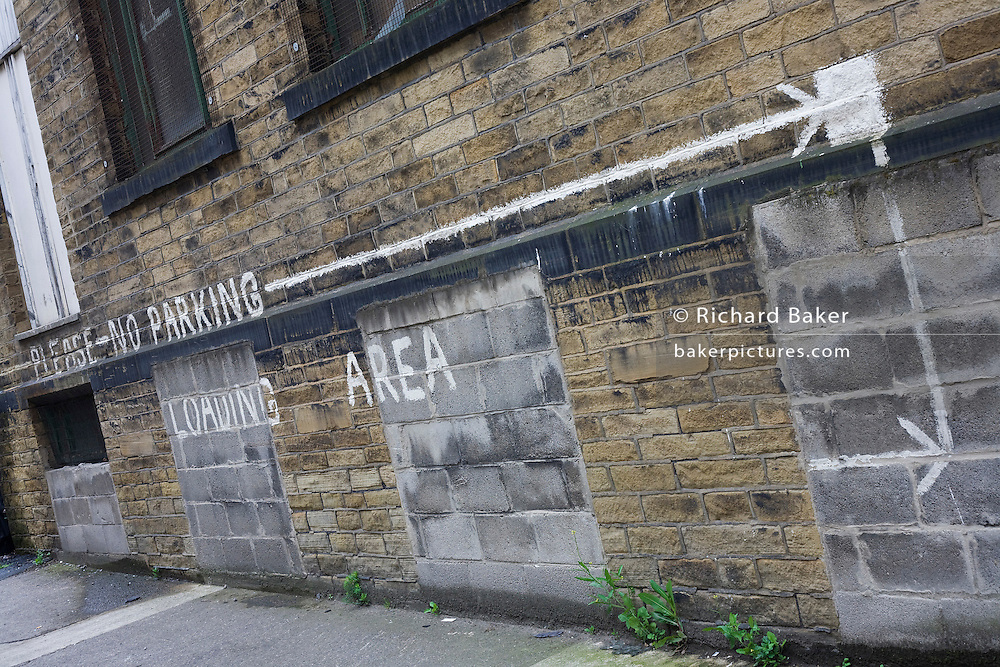 The words Please No Parking and Loading Area have been painted by hand on a wall of a warehouse-based business. The artist has also drawn a long arrow that stretches along the wall to mark the length of free area wanted in this quiet street near Bradford city centre, Yorkshire.