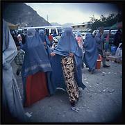Women wearing burqa walk in downtown Kabul.