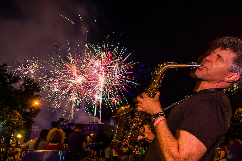 Saxophonist Nelson Rangell playing with Independence Eve fireworks over the City and County Building in background, Civic Center Park, Downtown Denver, Colorado USA.