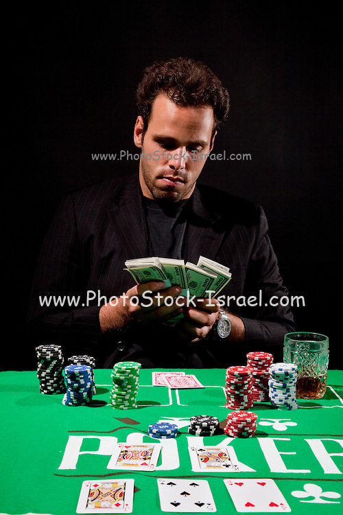 A young male gambler at the gambling table counts his money model release available