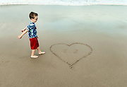 Young boy is pleased with his heart sand drawing in the beach sand.